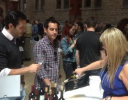 Michael Flaherty, left, and Jordan Levine of L'Albatross in Cleveland chat with from Leah Sullberg as she pours Michael Sullberg chardonnay.